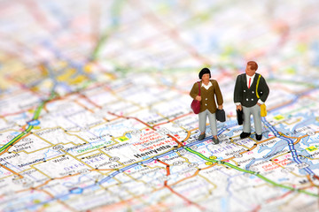 Miniature business travelers standing on a map.