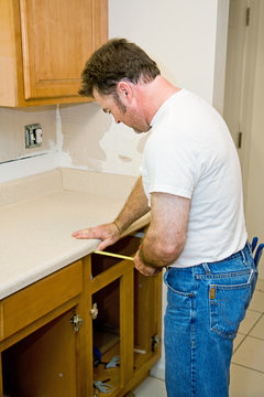 Carpenter remodeling kitchen is measuring the cabinets.