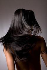 Beautiful dark hair from behind on grey background