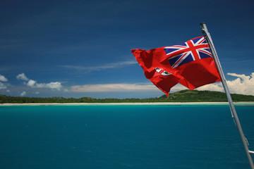 Fiji Flag flying over deep blue lagoon in the Yasawa Islands