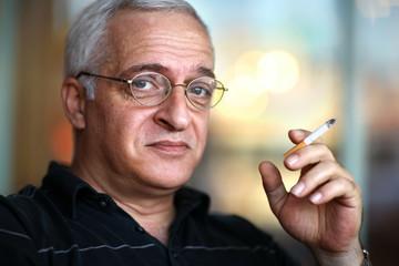 Elderly man smoking cigarette. Shallow DOF, focus on eye.