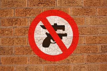 No weapons sign painted on brick wall