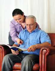 portrait of mature man and his wife holding book and reading