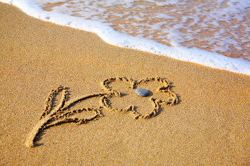 """""""Flower"""" drawing at sand, with sea wave"""