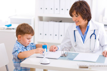 Senior female  pediatrician playing with child