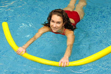 young woman  is swimming with aqua noodles