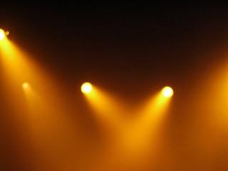 Spots colorés jaunes sur une scène de spectacle.