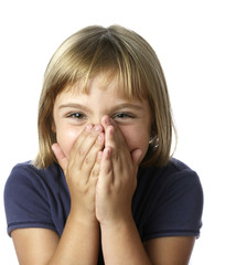 Blonde 7 year-old girl laughing with hands over mouth