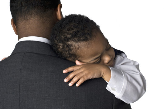 Portrait of an African American father holding his sleeping son
