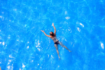 Blue water in the pool and girl.