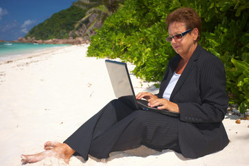 senior businesswoman with laptop working on the beach