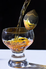 Glass with the poured liquid and an abstract lemon