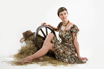 Young woman with wagon wheel, hay and hat