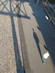 Promeneur et son ombre sur un quai de pierre.