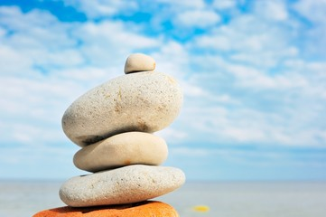 Stack of balanced pebbles, stones against colorful blue sky