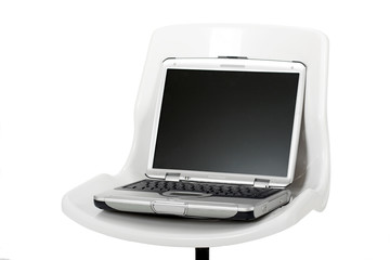 Picture of a laptop over a chair isolated on white