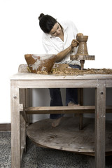 Picture of a potter works on a wood potter's wheel