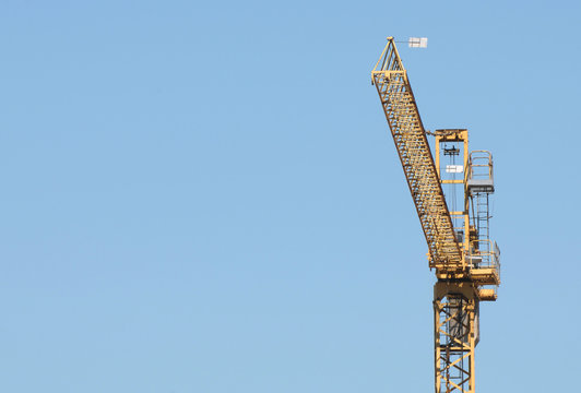 High section of a building crane over blue sky