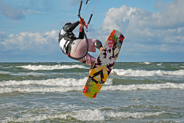 The kiting-man flies over waves.