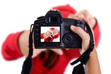 Girl taking photos to a young santa woman in christmas holidays