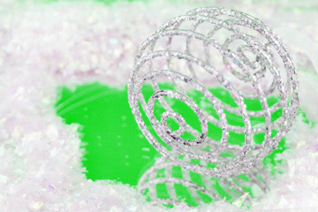 sparkly swirly  christmas ball with reflection on green