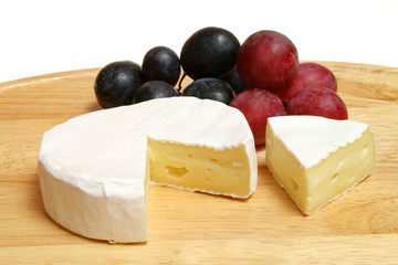 Camembert - soft cheese served on a wooden board with grapes