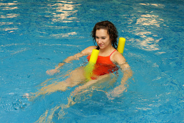 the girl is swimming on yellow aqua noodles