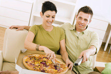 Couple eating pizza and watching TV at home.