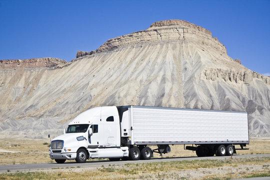 White semi truck driving in Colorado