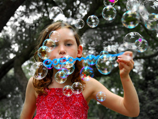 Young girl blowing lots of bubbles outside