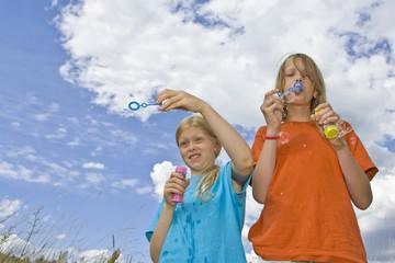 Children blowing bubbles on summer meadow
