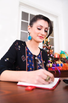 Smiling woman sitting at table, writing list