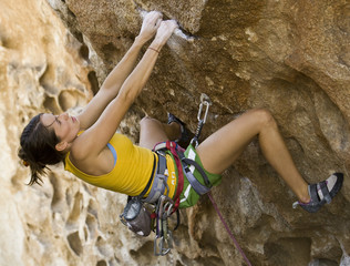 Female climber ascending an overhanging rock face.