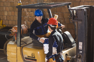 Two construction workers handshake.