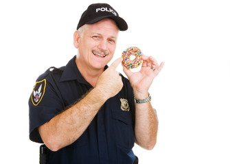 Policeman pointing to a delicious sprinkle covered donut.