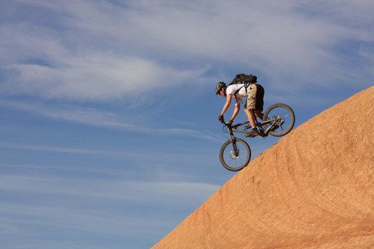 A fearless mountain biker drops down a steep trail.