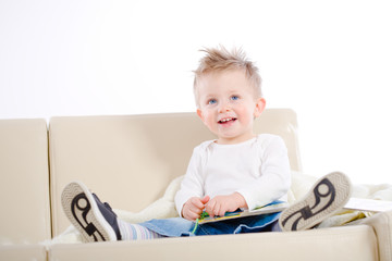 2 years old happy baby boy sitting on sofa reading story book