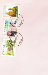 Collection of used Polish stamps on pink background