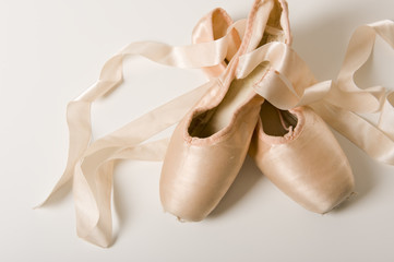 A pair of ballet shoes on a white background