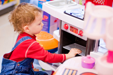 4-year old boy playing with toy kitchen