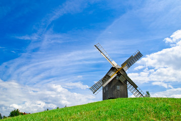 Wooden windmill against the summer blue sky with white clouds