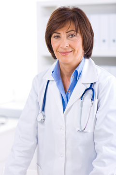 Portrait of senior female doctor working at office.