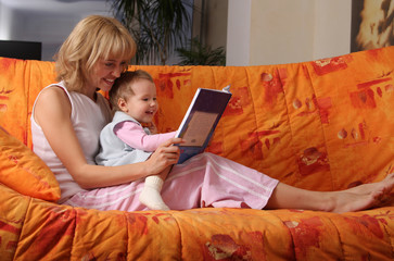 Mum reads the book to a daughter