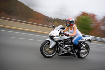 A pretty blonde girl in action driving a motorcycle