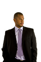 A black man in a nice suit with his hands in his pockets