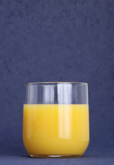 small glass of orange juice, blue background