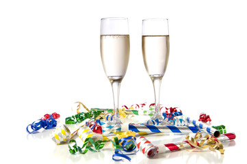 Two glasses of champagne with party noise maker and streamers
