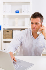 man working on computer at home calling on phone.