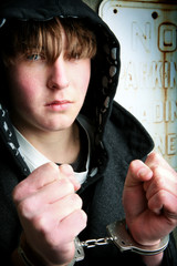 teenager in handcuffs - youth crime concept