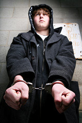 teen crime - portrait of young teenage in handcuffs